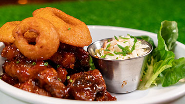 bbq wings with onion rings and coleslaw on the side