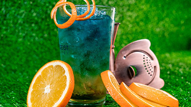 blue and green cocktail surrounded by orange slices and bartender tools