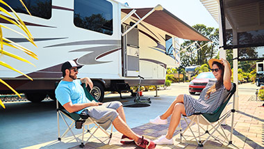 People sitting outside of a camper trailer