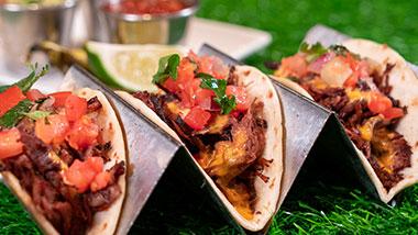 three chicken tacos topped with pico de gallo