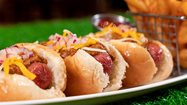 three hot dogs on a plate topped with cheese, chili and onions with fries in a basket in the background