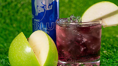 purple cocktail with apple slices next to it and a can of Red Bull in the background